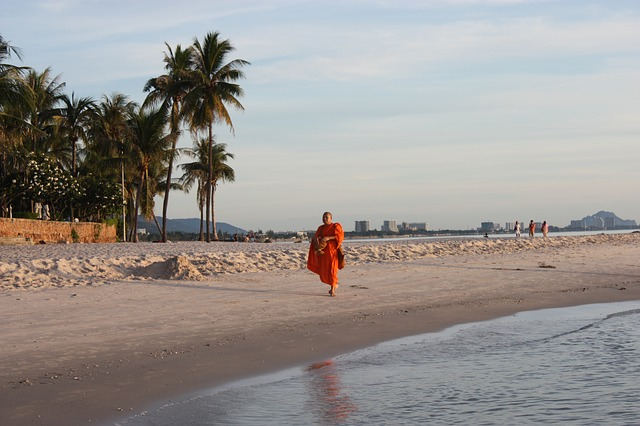 Un moine bouddhiste marche le long d'une plage à Hua Hin