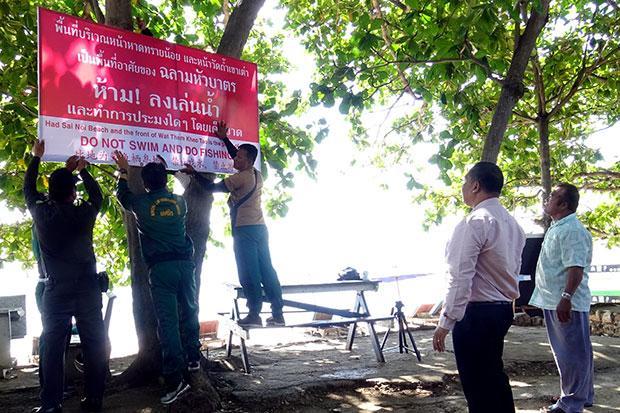 Un panneau est placé sur la plage de Sai Noi à Hua Hin, avertissant de ne pas se baigner ou pêcher dans la mer, où l'on a repéré des requins