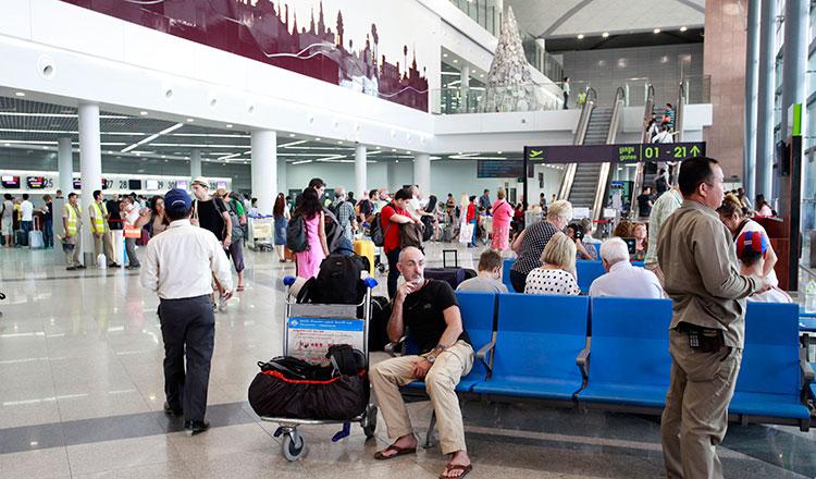 Des voyageurs cambodgiens et étrangers attendant devant les comptoirs d'enregistrement à l'aéroport de Phnom Penh
