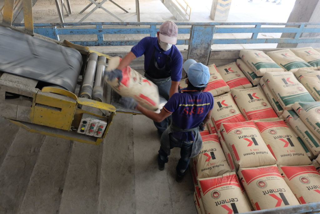 Workers at Siam Cement's Cambodian plant in Kampot load plastering cement onto a truck